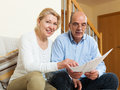 Mature couple with documents at home senior financial on sofa in Stock Photo