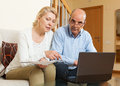 Mature couple with documents and laptop in home interior Royalty Free Stock Photos
