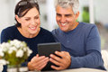 Mature couple emails reading on tablet computer Royalty Free Stock Image