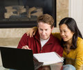 Mature couple enjoy working with each other at home photo of close looking information on the computer screen together fireplace Stock Photo