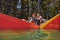 Mature couple enjoying a day at the lake active senior in two single kayaks side by side with women showing something interesting Royalty Free Stock Photo