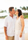 Mature couple enjoying sunset on the beach retired tropical vacation Royalty Free Stock Image