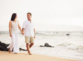 Mature couple enjoying sunset on the beach retired walk Stock Photography