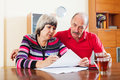 Mature couple fills in the questionnaire at home interior Stock Image