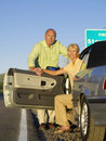 Mature couple getting out of car on roadside portrait Stock Photography