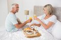 Mature couple having breakfast in bed happy at home Royalty Free Stock Image