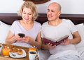 Mature couple having breakfast in bed joyful reading book while Royalty Free Stock Photos