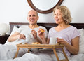Mature couple having breakfast in bed joyful smiling enjoying the morning focus on man Royalty Free Stock Image