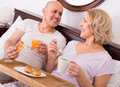 Mature couple having breakfast in bed positive healthy the morning Stock Photos