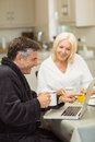 Mature couple having breakfast together man using laptop men at home in the kitchen Royalty Free Stock Image
