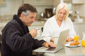 Mature couple having breakfast together man using laptop men at home in the kitchen Royalty Free Stock Photography