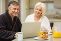 Mature couple having breakfast together man using laptop men at home in the kitchen Stock Images