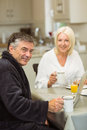 Mature couple having breakfast together man using laptop men at home in the kitchen Royalty Free Stock Photo