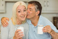 Mature couple having coffee together at home in the kitchen Royalty Free Stock Photography