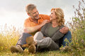 Mature couple having fun together happy laughing outdoor in the park Stock Photos