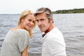 Mature couple having fun on a trip to the lake embracing each other bridge by Royalty Free Stock Photos