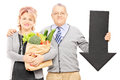Mature couple holding a paper bag full of groceries and big blac black arrow pointing down isolated on white background Stock Image