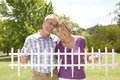 Mature couple holding small picket fence outdoors, smiling, portrait Royalty Free Stock Photo