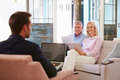Mature Couple At Home Meeting With Financial Advisor Royalty Free Stock Photo