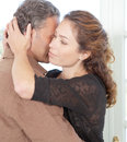 Mature couple hugging in living room. Stock Photos