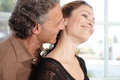 Mature couple kissing in living room. Royalty Free Stock Image