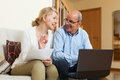 Mature couple with laptop in home smiling documents and interior Royalty Free Stock Images