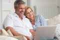 Mature couple with laptop portrait of happy sitting on couch using Royalty Free Stock Images
