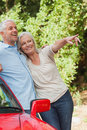 Mature couple leaning against their red cabriolet on a sunny day Royalty Free Stock Images