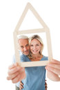 Mature couple looking through house outline portrait of happy over white background Royalty Free Stock Images