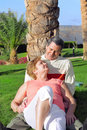 Mature couple lying in embrace near palm-tree. Stock Photography