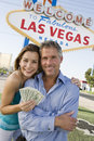 Mature Couple With Money And Welcome Sign In The Background Royalty Free Stock Photo