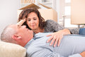Mature couple at new home happy laying on the sofa in their just after moving in Royalty Free Stock Image