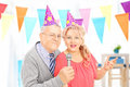 Mature couple with party hats singing at a celebration happy Royalty Free Stock Photo