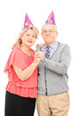 Mature couple with party hats singing on microphone isolated white background Stock Photos