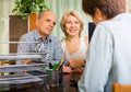 Mature couple of pensioners talking with employee at office Stock Image