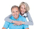 Mature couple on pilates ball woman embracing man from behind sitting Royalty Free Stock Images