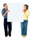 Mature couple presenting blank white billboard Royalty Free Stock Photos