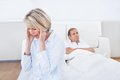 Mature couple in quarrel at home sad woman sitting the edge of bed front of man Royalty Free Stock Image