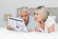 Mature couple reading newspaper in bed relaxed at home Stock Photo