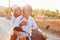 Mature Couple Riding Motor Scooter Along Country Road Royalty Free Stock Photo