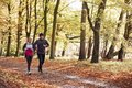 Mature Couple Running Through Autumn Woodland Together Royalty Free Stock Photo