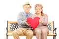 Mature couple seated on bench holding a big red heart isolated white background Royalty Free Stock Photography