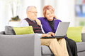 Mature couple seated on couch looking at laptop home Stock Images