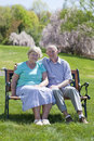 Mature couple sitting and smiling outdoors in sunshine Royalty Free Stock Photo