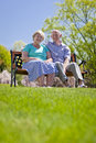 Mature couple sitting and smiling outdoors in sunshine Royalty Free Stock Image