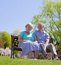 Mature couple sitting and smiling outdoors in sunshine Stock Photos
