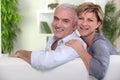 Mature couple sitting on sofa Stock Image