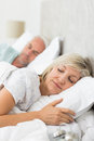 Mature couple sleeping with eyes closed in the bed closeup of a at home Royalty Free Stock Photo