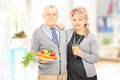 Mature couple standing close together holding a healthy food and drink at home Royalty Free Stock Photo