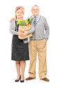 Mature couple standing close together and holding a paper bag fu full length portrait of full of groceries isolated on white Stock Photo